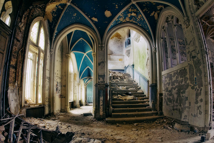 The hallway and stairway of a castle, fallen into disrepair and dilapidated.