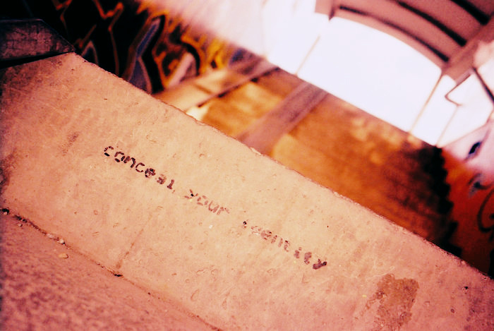 A concrete step with stencil reading 'conceal your identity.'