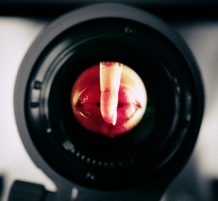 Lips pictured through a camera lens, making the 'shh' gesture.