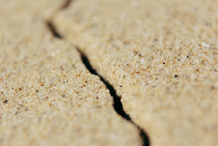 Sand, with a dry, cracked chasm splitting it.
