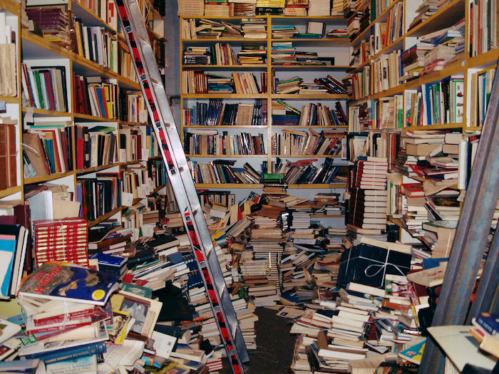 Hundreds of books piled on the floor and in bookshelves.