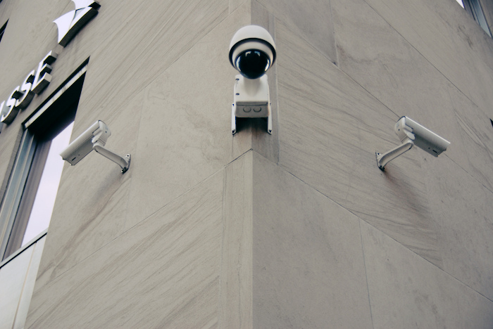 Surveillance cameras on the side of a marble wall.