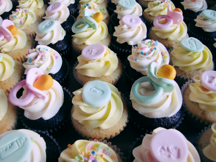 Cupcakes adorned with baby-themed decorations, like pacifiers and bows.