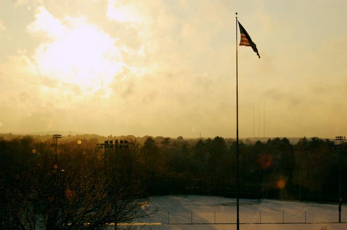 American flag mounted high over an urban setting.