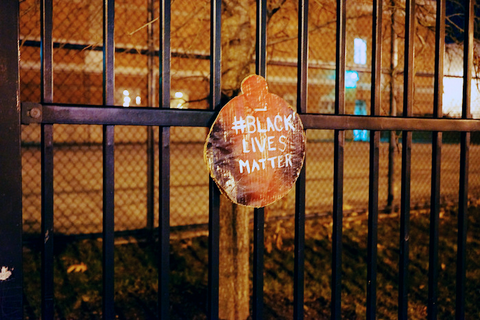 Sign with the hashtag blacklivesmatter painted on it.