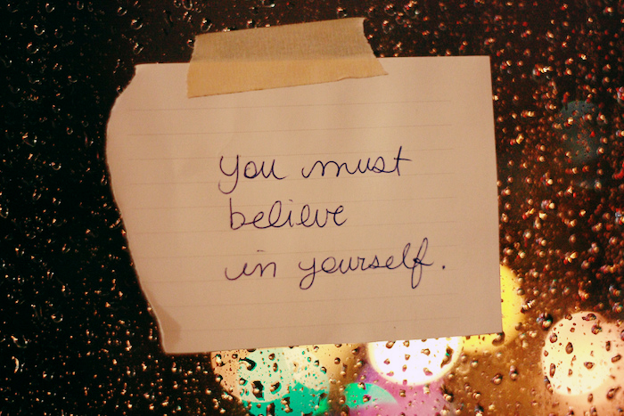 Note taped to a window reading 'You must believe in yourself'.