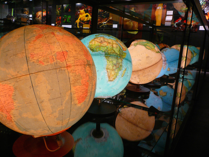 Series of globes in a museum display.