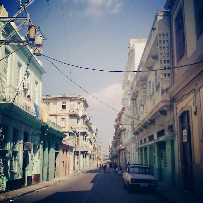 A street in Cuba, electric wires hanging in between lines of storefronts and residences. It's a beautiful sunny day and people are walking down the street in the distance.