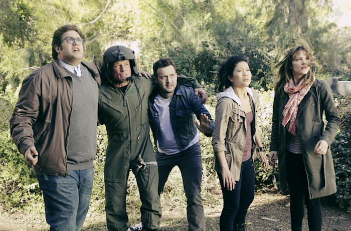 Cast of Scorpion gathered together in a wooded area.