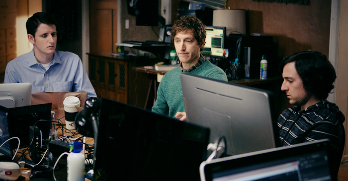 Male cast members of Silicon Valley sitting around computers in an office space.