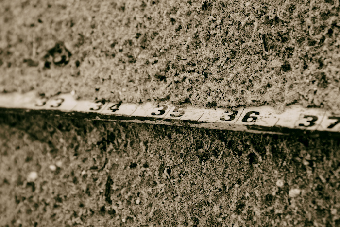 A ruler in the sand, with 34, 35 and 36 inch demarcations.