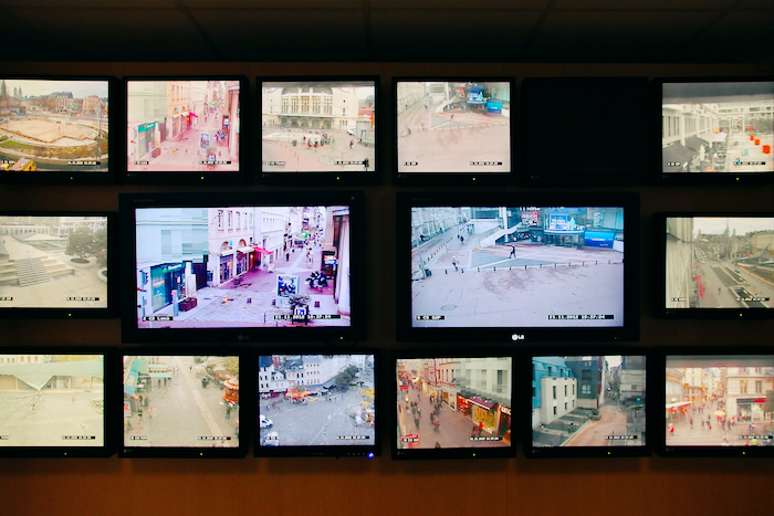 Multiple surveillance feeds displayed across many screens.