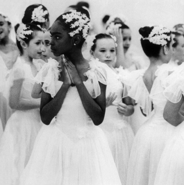 A group of young girls, all wearing lacy, floaty dance dresses with flowers in their hair. The camera is focused on the only young black girl in the group, her hands clasped together and looking off-camera. Image via Tumblr account blackgirlsarefromthefuture via wocinsolidarity.