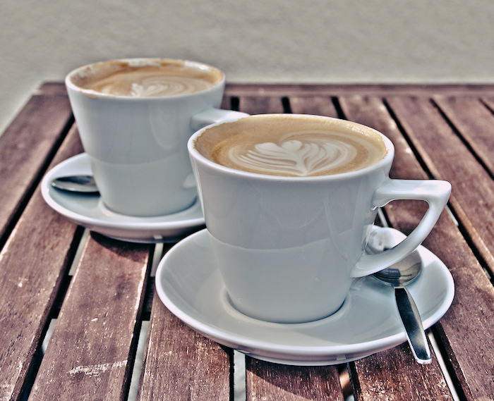 Two cups of coffee with hearts in the foam.