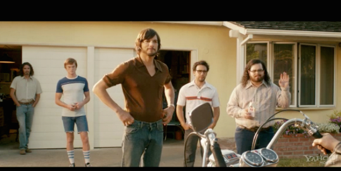 Still from the Jobs movie, showing four white men standing outside a garage.