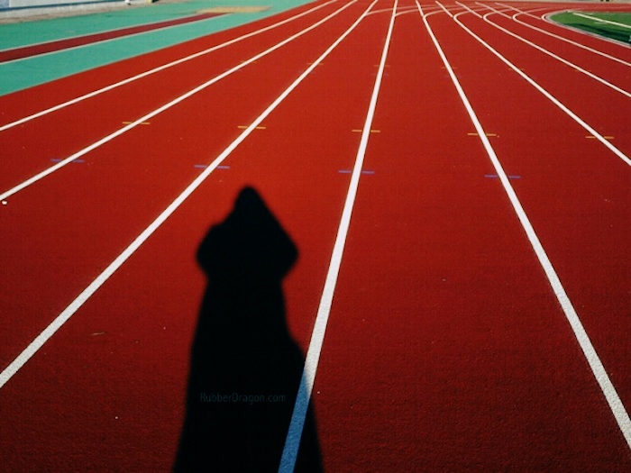 A running track with the shadow of a runner cast on it.