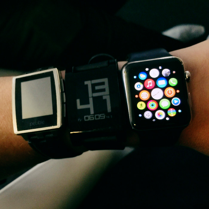 Three different smart watches on a single wrist.