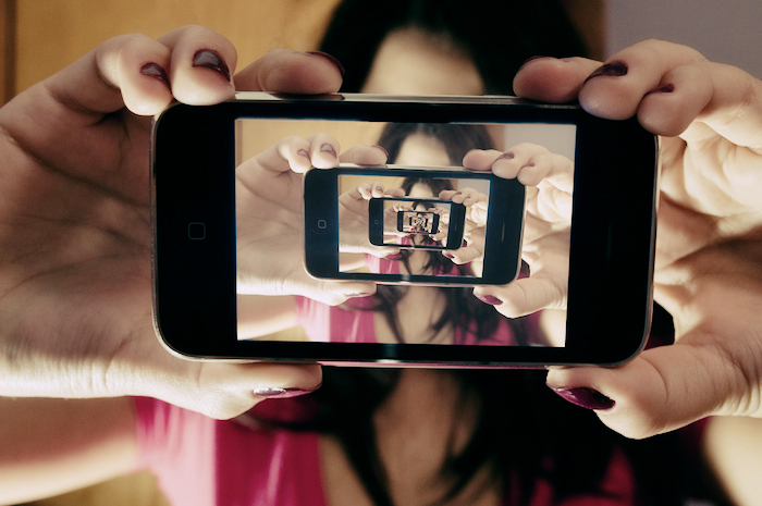 A woman holding up a camera phone in front of her face. Displayed on the phone is an inception-style repeat of the image, folding into itself infinitely.