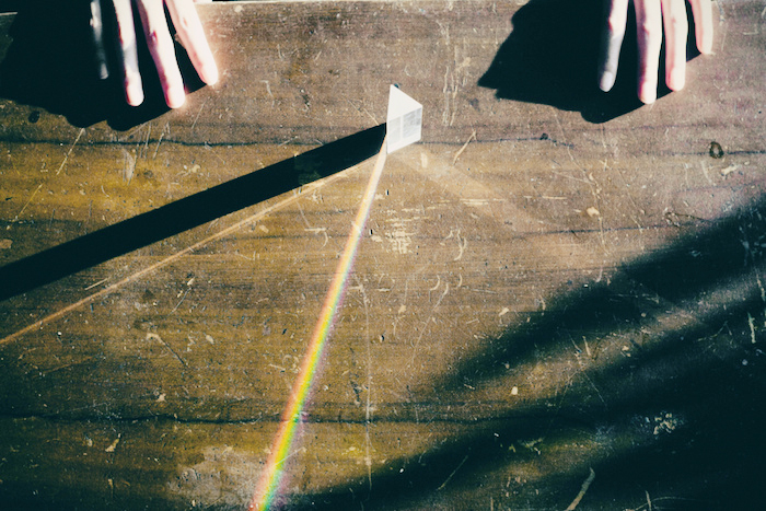 A prism positioned between two hands, reflecting beams of rainbow light.