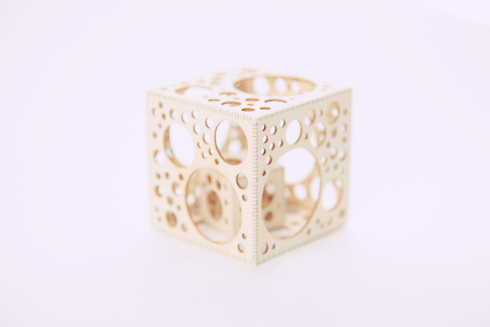 A cube with intricate, geometric cut-outs in its edges.