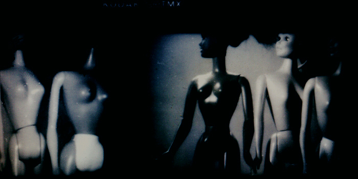 Silhouettes of un-dressed Barbies in black-and-white - the image is creepy and full of threatening shadows.