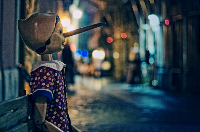 Statue of Pinocchio on a street in dusk.