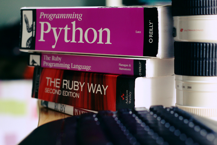 A stack of programming books, including Programming Python and The Ruby Way.
