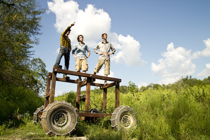 Three people standing on a skeletal wooden tractor, pointing upward. The scenery is lush and green, with a vast blue sky.