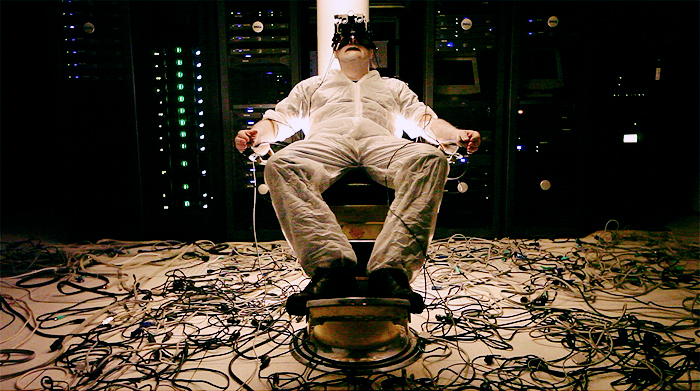 A man reclining in a chair, with virtual reality headgear, numerous wires attached to his body, flanked by large amounts of blinking computer equipment.