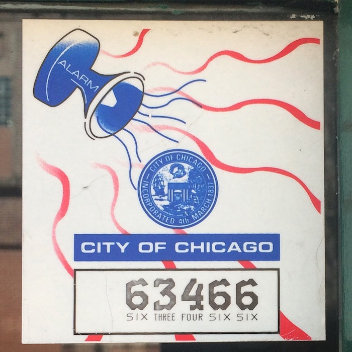 Business license with the seal of the City of Chicago affixed to it. In the upper left is a graphic of a megaphone with the text 'Alarm', sound waves emanating from it.
