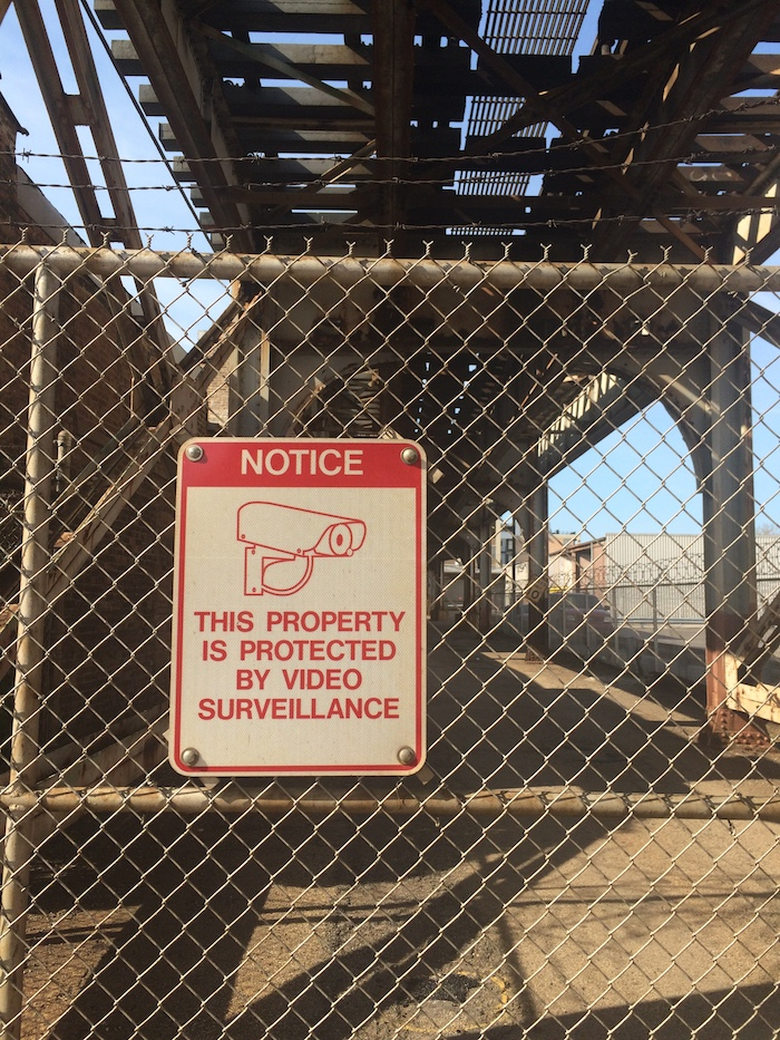 A fence with signage reading 'This property is protected by video surveillance.'