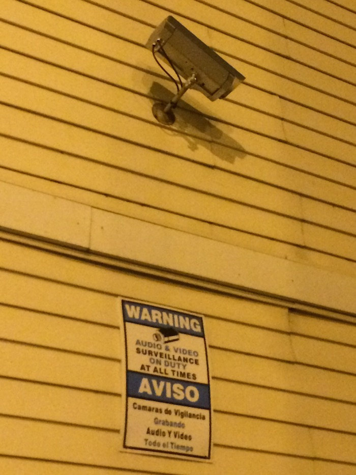 Side of a building with a surveillance camera and a sign reading 'Warning: Audio & Video Surveillance On Duty At All Times'. The message is also printed in Spanish.