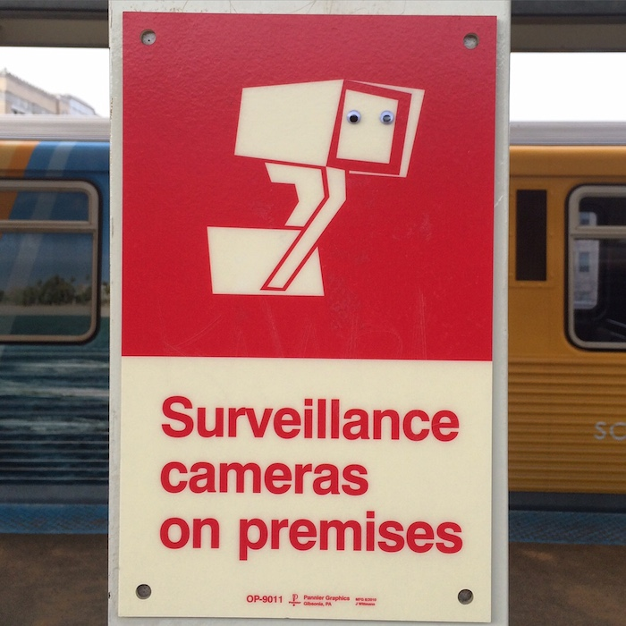 Signage on a train platform reading 'Surveillance cameras on premises', with a graphic of a camera. Someone has placed two googly-eyes on the lens of the camera.