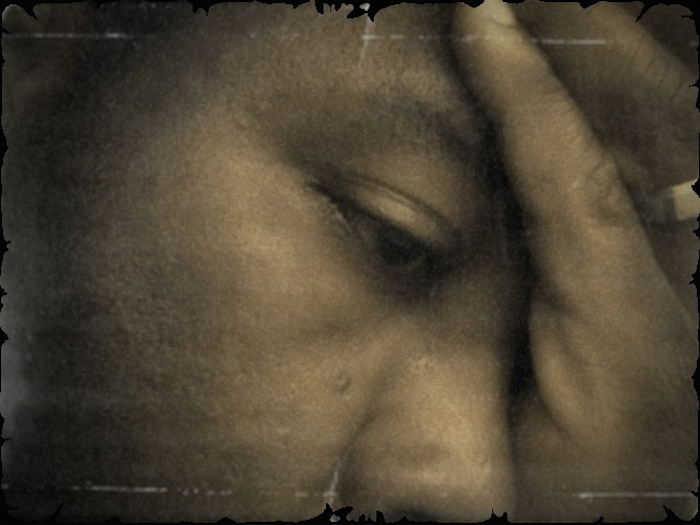 Portrait of a black man, forehead resting in his hands and eyes downturned.