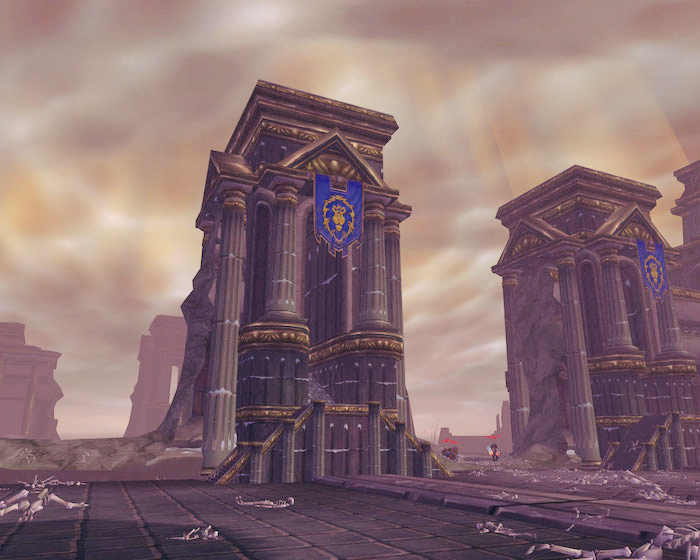 The Wintergrasp Fortress in World of Warcraft: Two large, pillared buildings with blue banners. Character corpses lie all around.