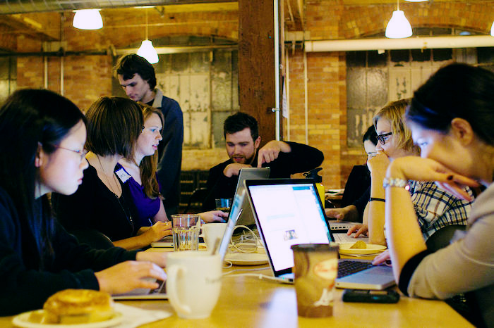 Photo of a group of coders, primarily women, working around a table.