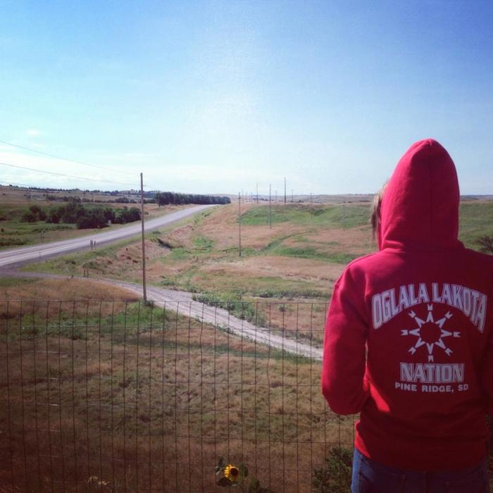 "Photo of the author standing behind a wire fence and looking out over roads, fields and hills in Pine Ridge, SD. Her back is to the camera and her red sweatshirt reads ""Oglala Lakota Nation."""