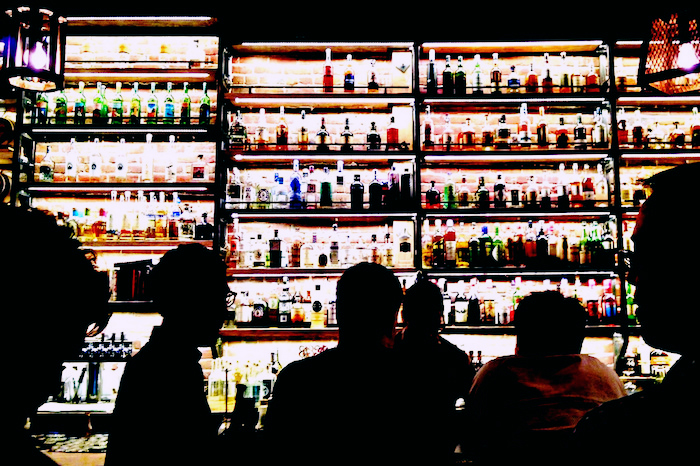 Rows and rows of alcohol on the shelves of a bar.