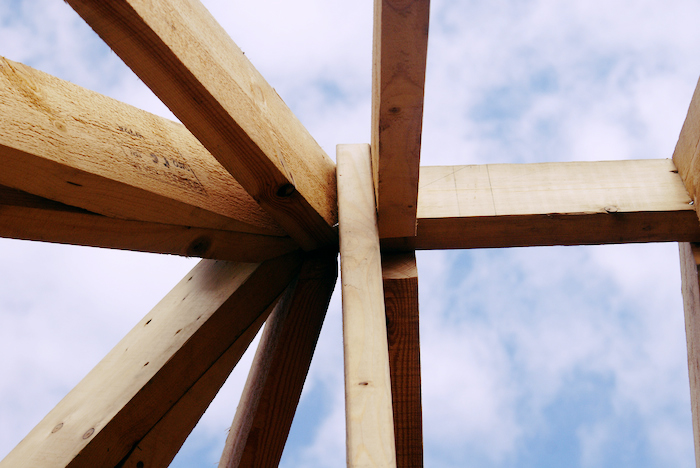 Image of a bare wood infrastructure against the sky.