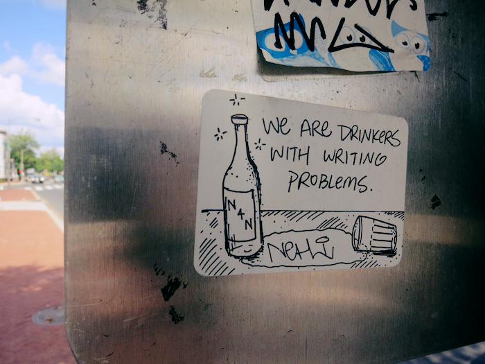 Photo of a sticker on a metal wall reading 'We are drinkers with writing problems', and a doodle of a bottle and spilled glass.