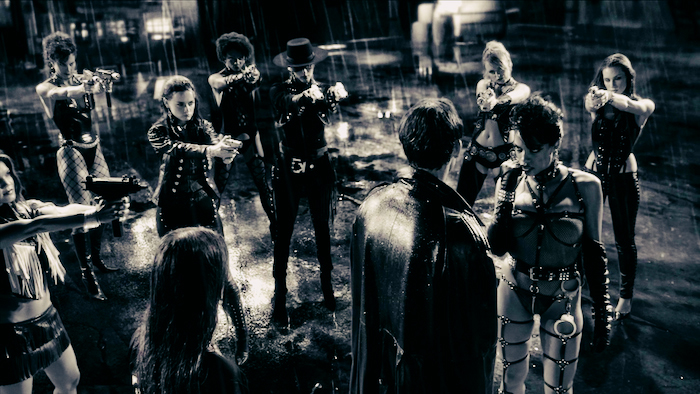 Still from Sin City. The Girls of Old Town gather around a man, all pointing guns at his head.