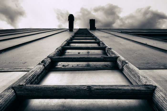 Artsy photo of a ladder leading up a 90-degree wall, smoke billowing at the top.