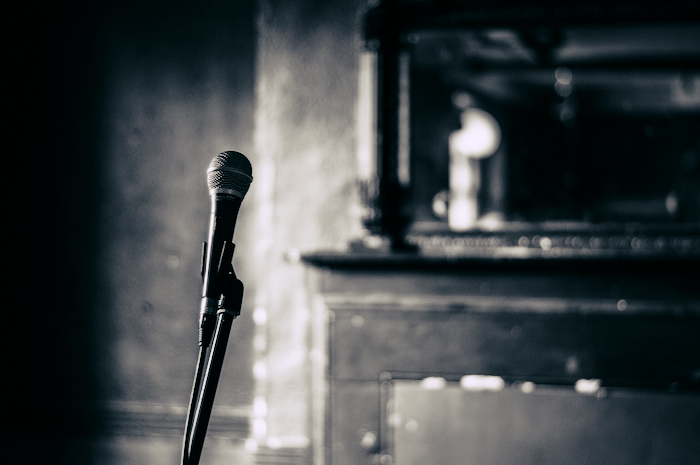 A microphone standing in a bare, bleak room.