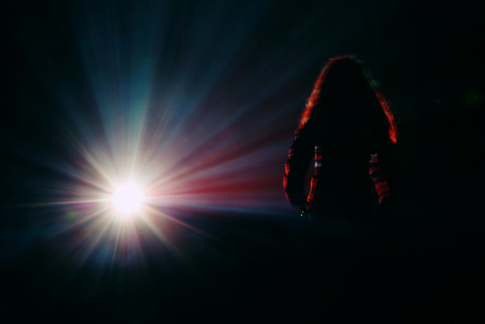 A person with long, curly hair on a stage all alone, facing a bright light.