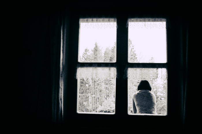 A woman sitting and facing snow-covered trees, pictured through a 4-pane window.