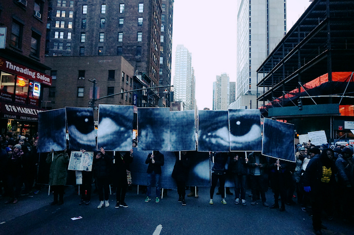 Photo of the Millions March march for justice for victims of police violence in NYC. Protestors hold signs that together form Eric Garner's eyes, staring out from the crowd and streets.