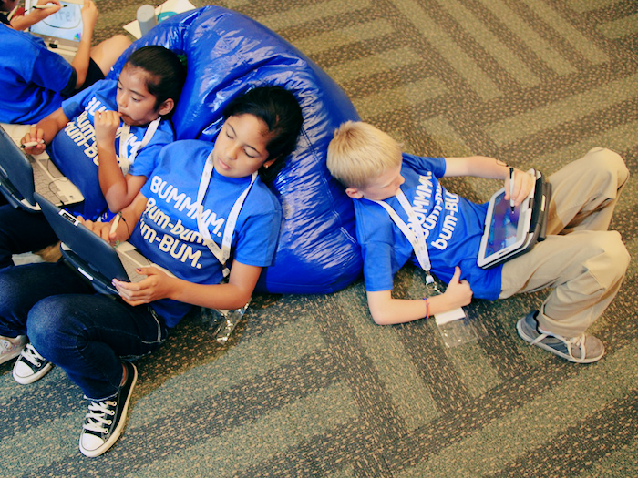 Young children lounging on a beanbag, playing with their tablet devices.