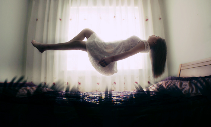 A woman, floating or levitating above a bed, dark lights reaching from the mattress while she floats in light.