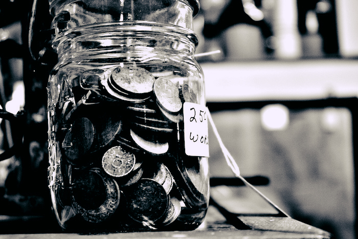 Pennies and other coins in a mason jar.