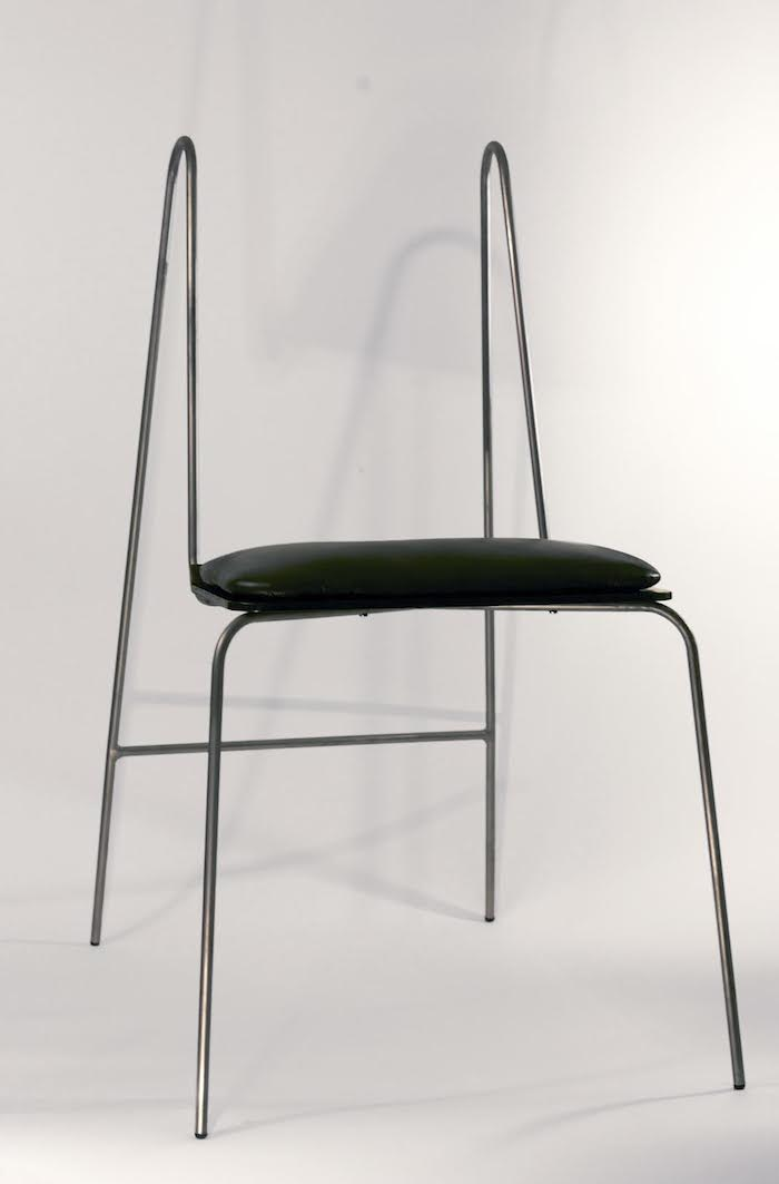 A chair with thin, clean, wiry legs and no back rest or padding.